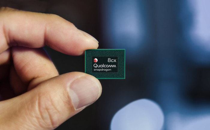 Hand holding up a Snapdragon 8cx chip
