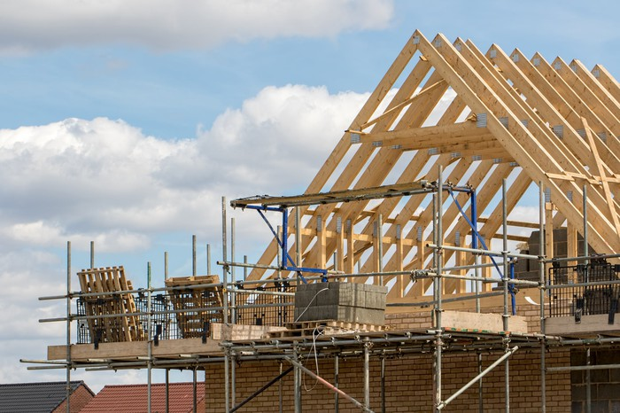 A timber A-frame roof of a residential home is shown under construction against a cloudy blue sky.