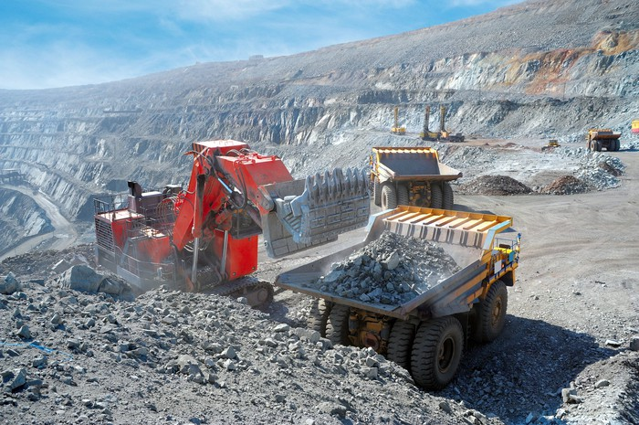 A large machine loads ore onto the back of a dump truck.