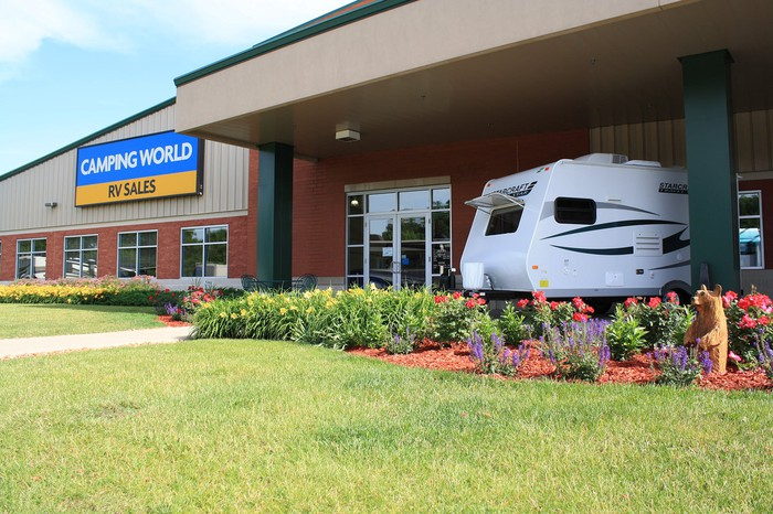 Camping World location with RV parked out front and colorful flower beds.