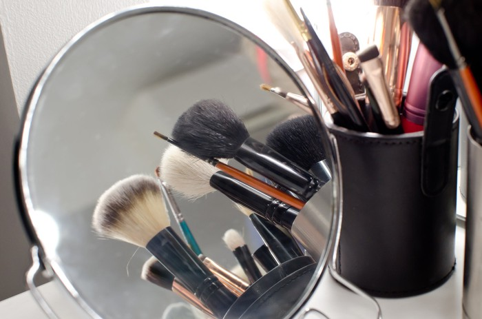 Makeup brushes and a mirror.