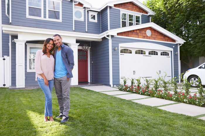 Smiling man and woman standing in front of house