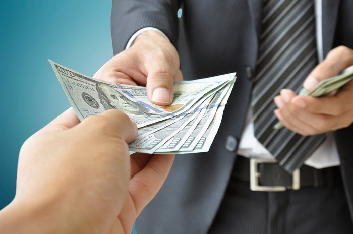 A man handing over a fanned stack of one hundred dollar bills to an outstretched hand.