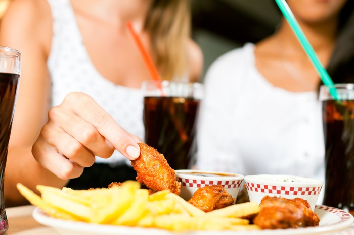 Two women eating chicken wings with sodas.