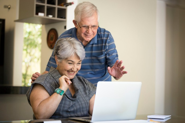 An older couple looks excitedly at a laptop screen.