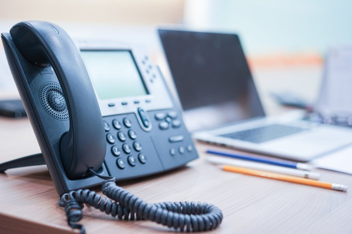 An office phone system sitting on a desk.