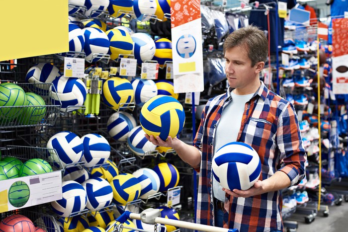 A man holding two volleyballs in a sporting goods store.