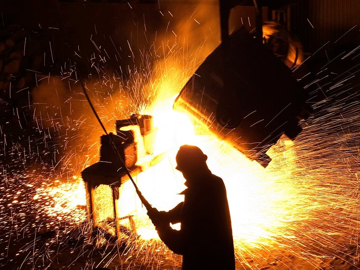 A worker in a steel plant, sparks flying in front of him.
