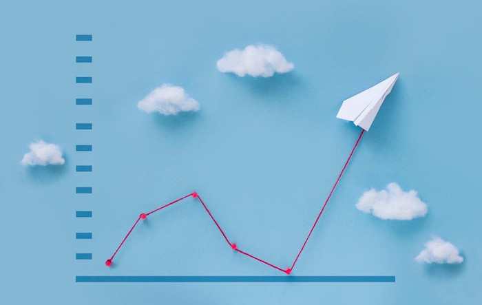 A paper airplane traveling upward on a graph with clouds in background.