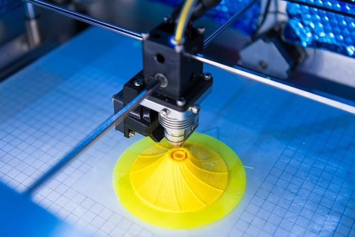 Close-up of a 3D printer printing a yellow plastic object on a blue-lighted surface.
