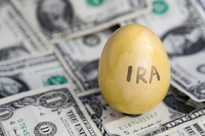 A golden egg with the word IRA written on it that's sitting atop a messy pile of one dollar bills.