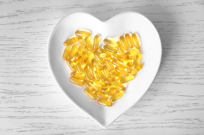 Numerous fish oil pills in a bowl shaped like a heart.