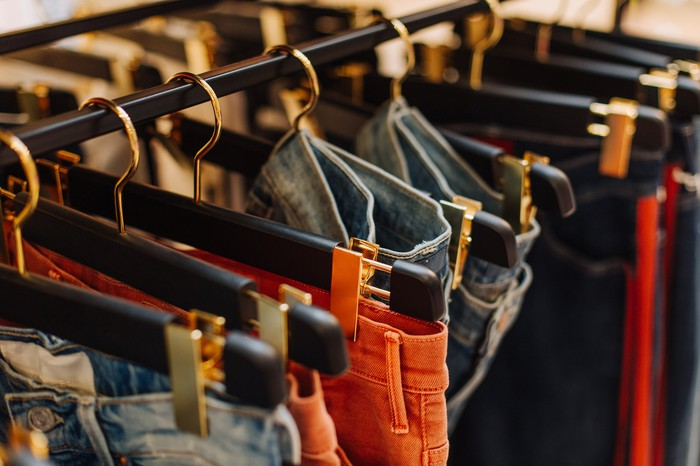 Colorful assorted blue jeans on a rack in a boutique clothing store.