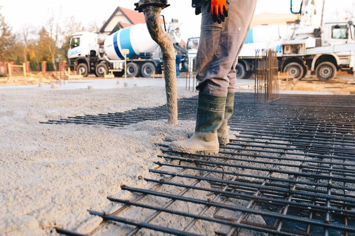 A worker guiding a concrete pour from a boom truck.