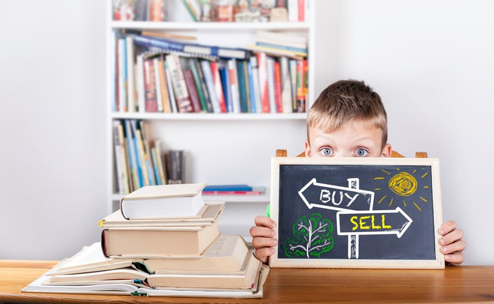 "A child holds a blackboard with ""buy"" and ""sell"" arrows drawn across it."