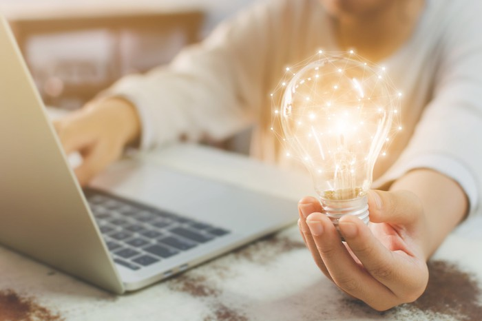 A woman holding a light bulb in one hand while using a laptop.