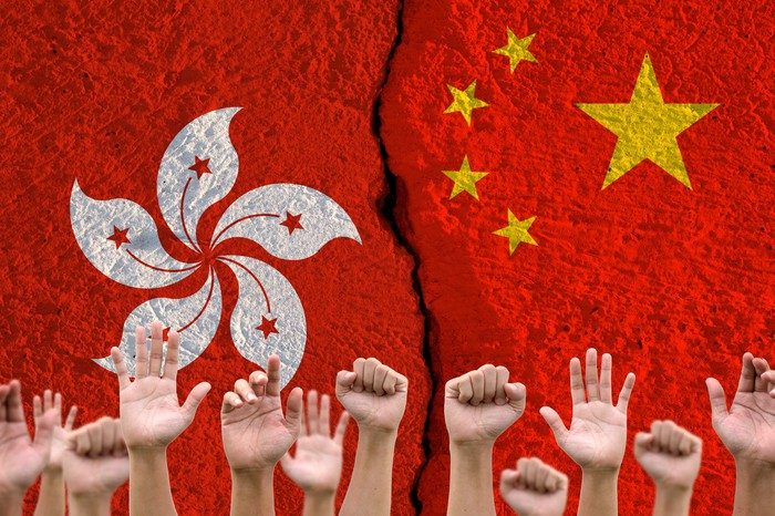 Raised hands with the flags of Hong Kong and China in the background.