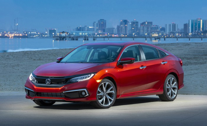 A red 2019 Honda Civic, a compact sedan, parked with a city skyline in the background.