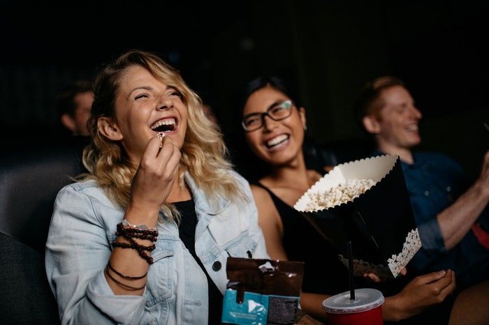 Two women eat popcorn in a movie theater.