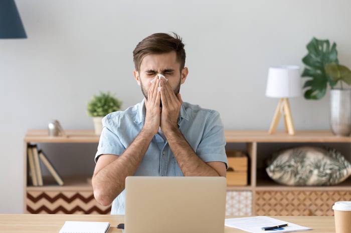 Man sitting at laptop, blowing his nose