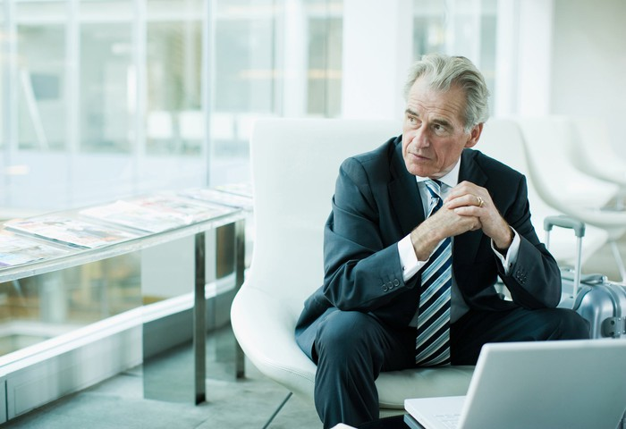 Older man in business suit sitting in airport waiting area
