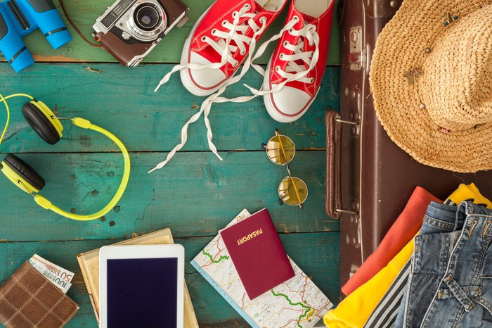 A collection of travel accessories, including shoes, a camera, a passport, and a tablet.