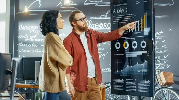 Man and woman look at financial analysis chart on a board