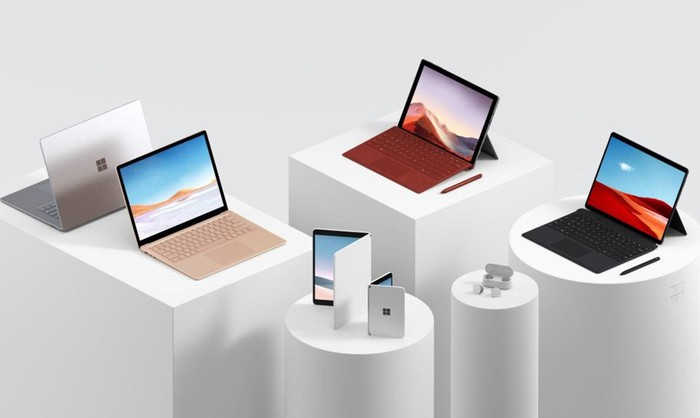 Microsoft tablets, computers, and a phone sitting on white pedestals.