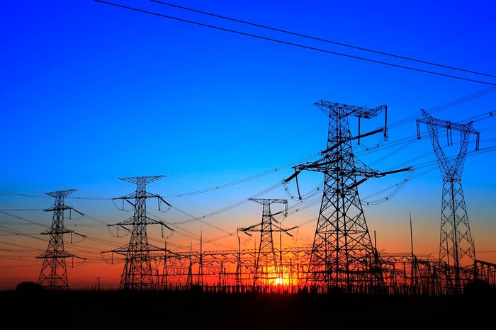 Complex of power line towers and transformer equipment with sun setting in the background
