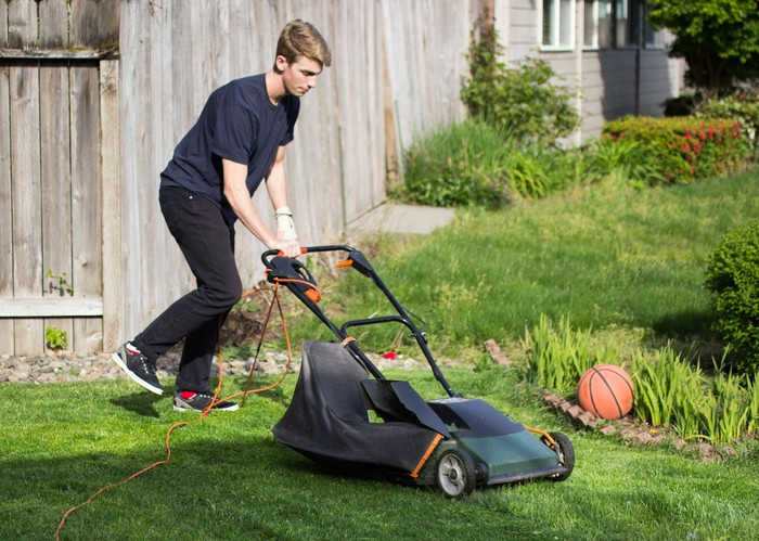 A young man mowing the lawn.