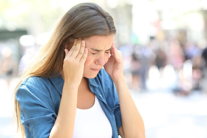 Woman holding her head with a pained expression.
