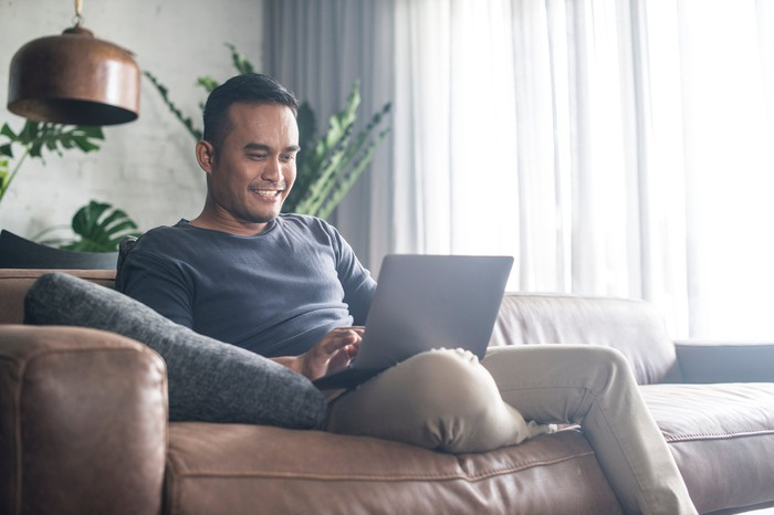 Smiling man sitting on couch, typing on laptop