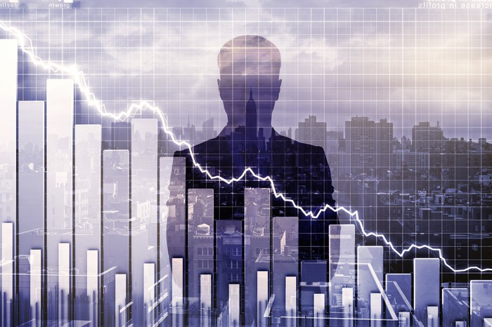 A silhouette of a man looking over a stock chart.