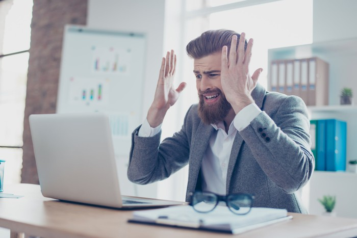 Professionally dressed man at laptop holding his hands up as if frustrated