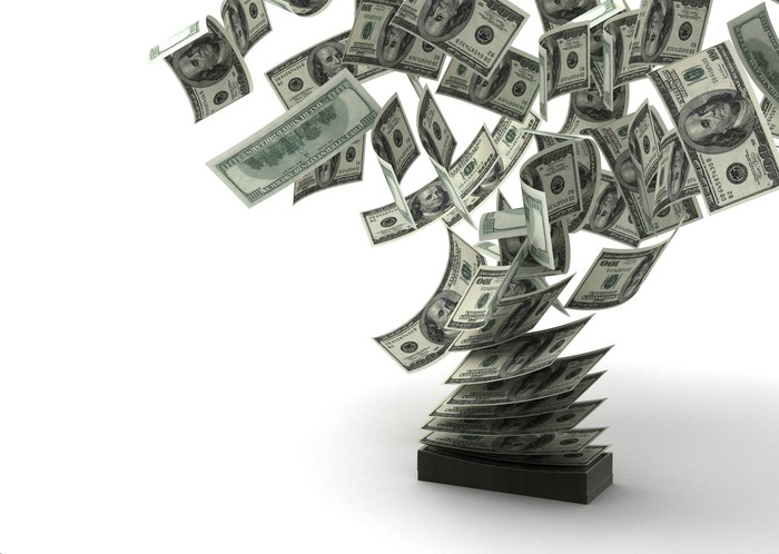 $100 bills being blown away from a stack of money