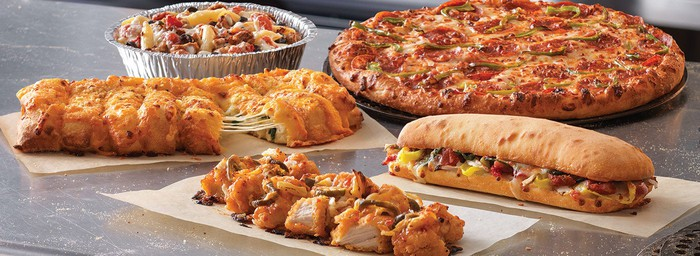 A Domino's pizza, sandwich, chicken wings, and cheesy bread displayed on a table.