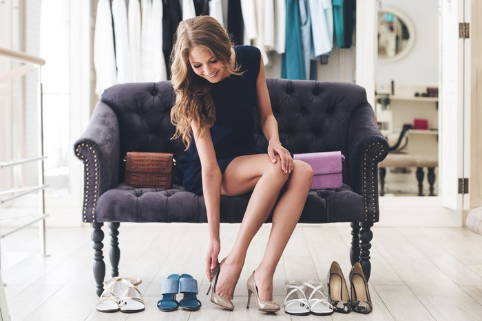 A young woman trying on high heels in a boutique.