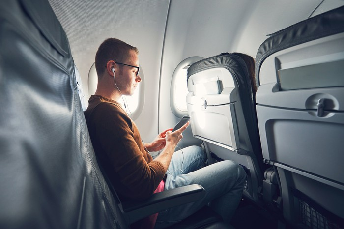 A young man looking at his smartphone, seated in an airliner.