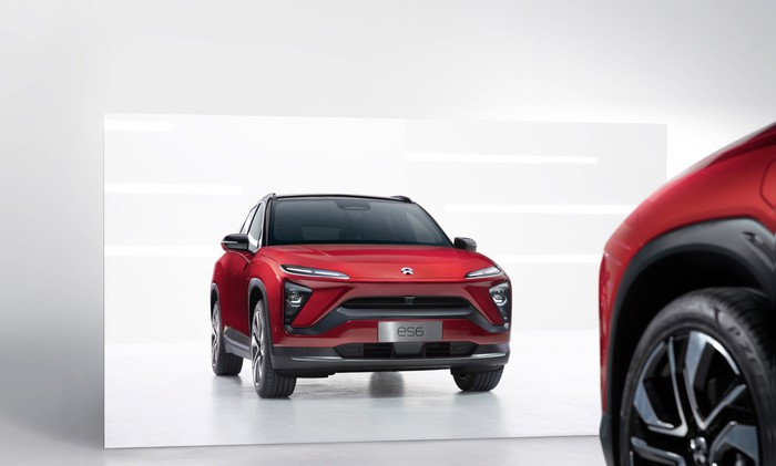 A NIO ES6 SUV in red, pulled up to and reflected in a mirror.