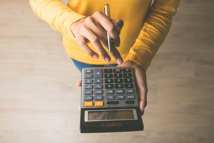 A woman in a yellow sweater using a calculator.