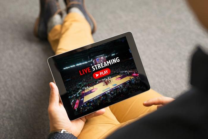 A man streams a live NBA game on a tablet.