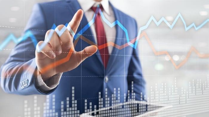 A businessman touches a digital financial chart.