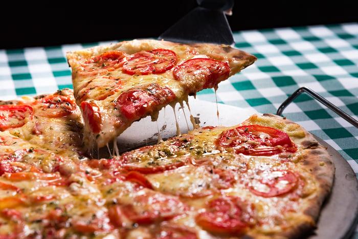 A spatula lifting a slice of pepperoni pizza