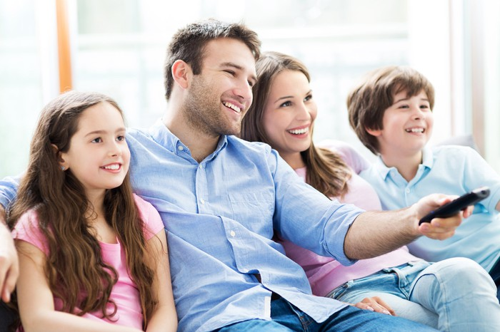 A family of four sitting on a couch; the man holds a TV remote control.