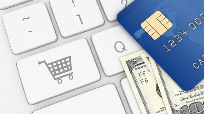 Credit cards and cash next to a shopping cart button on a keyboard