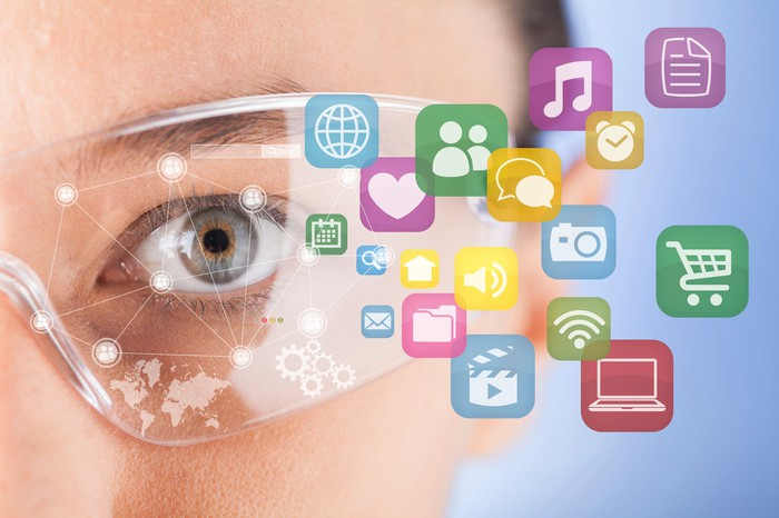 Person wearing AR glasses with various app icons projecting from them