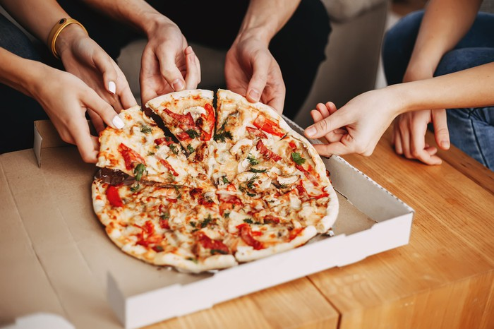 A close-up of several friends removing pizza slices from a delivery box.