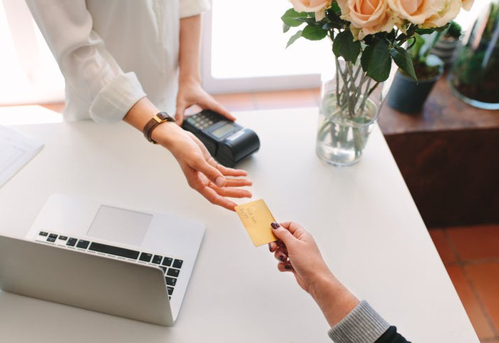 A woman's hand handing a credit card to a woman behind a desk that has a payment processing device and laptop on it.