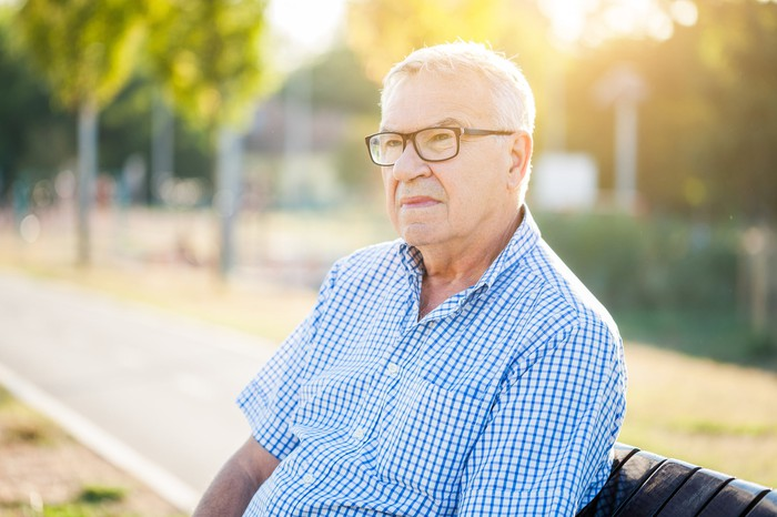 Senior man with serious expression sitting outdoors