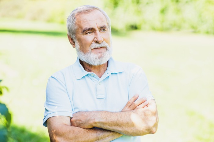 Older man outdoors with arms crossed, sporting disappointed expression.